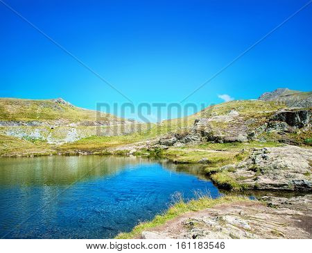 lake in the mountains under a beautiful blue sky