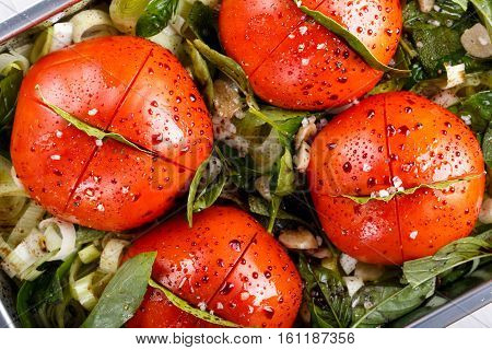 Whole tomatoes with leek garlic balsamic vinegar olive oil and herbs on a baking tray. Vegetables ready for roasting in the oven.