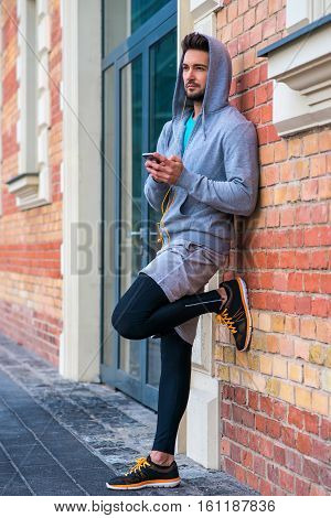 A handsome young sportman leaning to a brickwork while using his phone