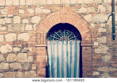 close up of a curtain on an old door in Tuscany Italy