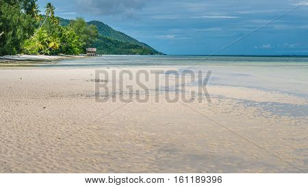 White Sand during Low tide, Water Hut of Homestay in Background on Kri Island. Raja Ampat, Indonesia. West Papua poster
