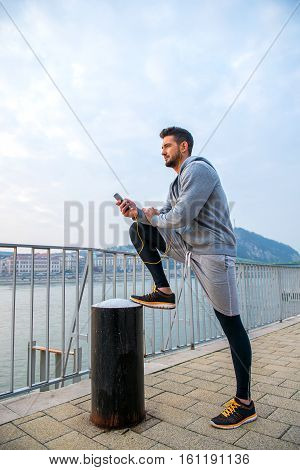 A handsome young man putting his leg up and leaning on it while using his phone at the riverside