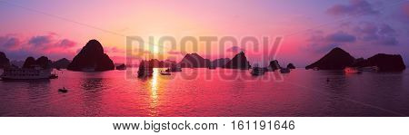 Beautiful purple sunset and rock islands in Halong Bay Vietnam Southeast Asia. Panorama. Junk boat cruise to Ha Long Bay. Exotic scenery. Panoramic view. Landscape Pink sky. Famous landmark of Vietnam poster