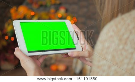 Woman looking at horizontal tablet computer with green screen. Close up shot of woman's hands with pad. Elegant abstract garlands bokeh background