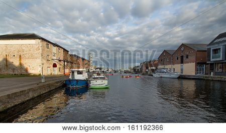 Moored in the harbor of ships and people kayaking. Exeter. England