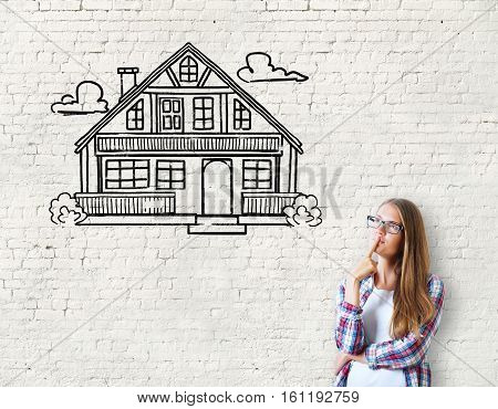 Attractive caucasian girl on brick background with house sketch. Real estate mortgage and housing concept