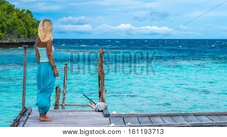 Blond Girl Staying on Wooden Pier of an Homestay looking into blue ocean, Gam Island, West Papuan, Raja Ampat. Indonesia