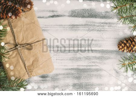 Gift wrapped craft paper with pine cones and fir branches on the wooden shabby chic table top view copy space at the right
