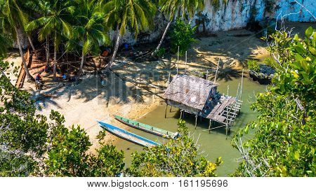 Local people tap new location, Bamboo Hut and Boats on Beach in low Tide, Kabui Bay near Waigeo. West Papuan, Raja Ampat. Indonesia
