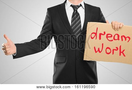Businessman with cardboard poster showing thumbs up on grey background. Dream work concept