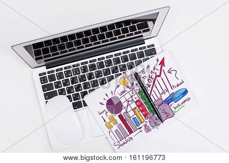 Top view of laptop computer mouse and notepad with colorful financial sketch. Business concept