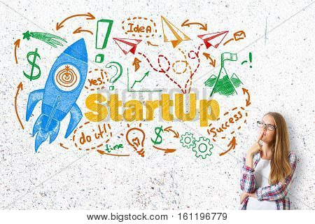 Thoughtful caucasian girl on concrete background with creative rocket ship sketch. Startup concept