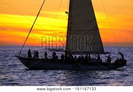 Sailboat sunset party is a group of people having a good time sailing at sunset across the ocean.