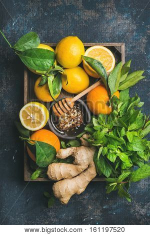 Ingredients for making immunity boosting natural drink. Lemons, oranges, mint, ginger, honey in wooden box over dark blue background, top view. Clean eating, healthy lifestyle, detox, dieting concept