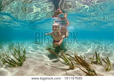 Happy family - mother with baby son dive underwater with fun in sea pool. Healthy lifestyle active parent people water sport outdoor adventure swimming lessons on beach summer holidays with child
