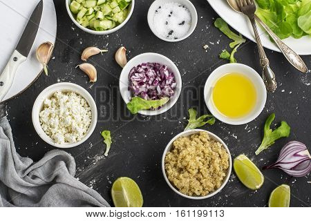 Ingredients for salad - quinoa and vegetables on a dark background. Delicious vegetarian food