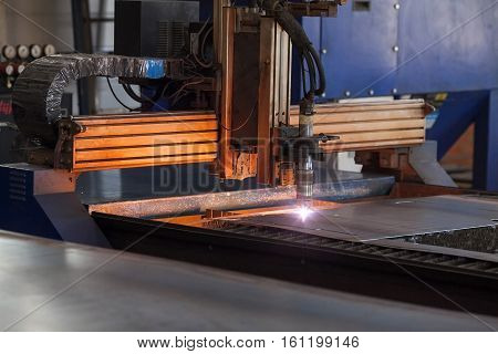 the modern powerful metal cutting laser mashine at factory. closeup of the automatic plasma robot in the course of metal cutting. Modern production of metal details.