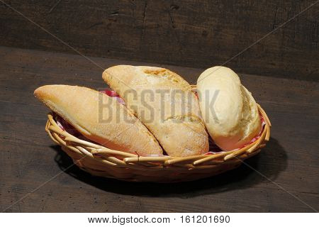 Various types of bread rolls cakes bun in a basket on a rustic wooden surface