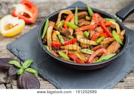 Sauteed beef with vegetables in a pan. Wooden background.
