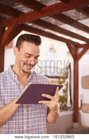 Cool dark haired guy looking at his tablet with a happy smile while he is in front of a big wood framed window