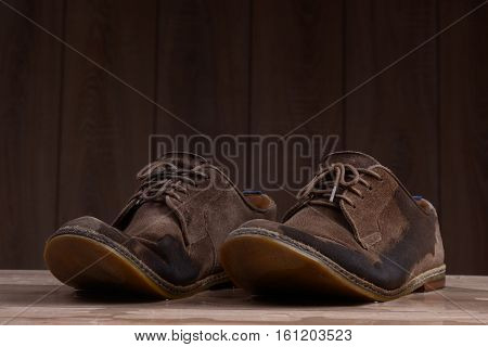 Wet brown suede shoes with brown laces on the background of dark natural wood.