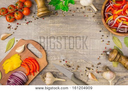 Ingredients for food onion pepper garlic and utensils on a wooden table. A top view of a plate of vegetables greens for copy space