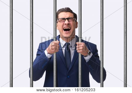 Young businessman behind the bars in prison poster