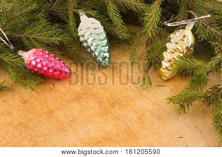 The branches of Christmas trees and fallal cone decorations on the background of wooden boards. Christmas and New Year's background.
