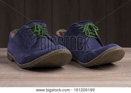 Blue suede shoes with green laces on the background of dark natural wood.