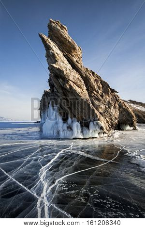 Lake is covered with a thick layer of ice. Ice story. Stone rock sticking out from under the piles of ice. The cleanest lake in the world, lake Baikal
