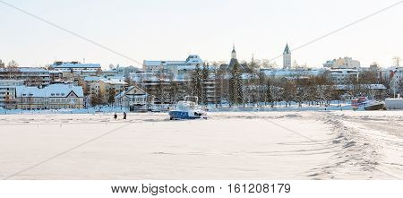 LAPPEENRANTA, FINLAND - FEBRUARY 18, 2010: Winter landscape with boats in harbor on Saimaa Lake and buildings in historical part of the city