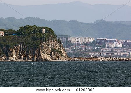 Cape with the lighthouse in the background of the city of Nakhodka Russia