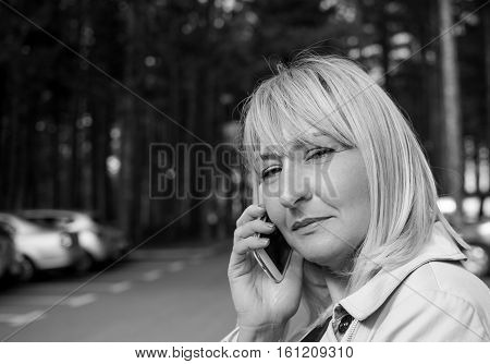 Middle aged woman talking on a mobile phone. Looking at the camera, with mobile phone in the hand. Black and white photo. Photo was taken outside.
