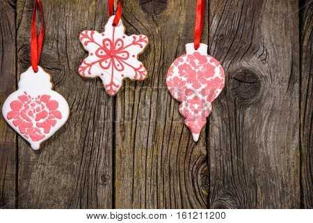 Gingerbread Cookies Hanging Over Wooden Background