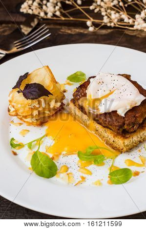 Dish with meat steak on toast, potato chips with melted cheese and poached egg with Dutch sauce