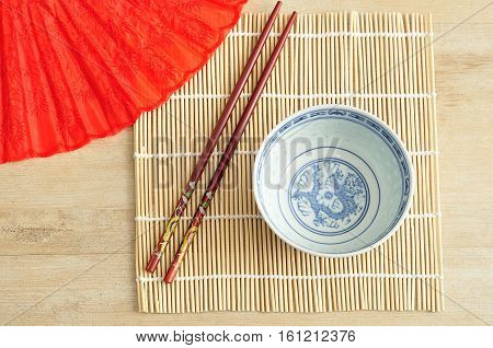 Chines bowl chopsticks and a hand fan