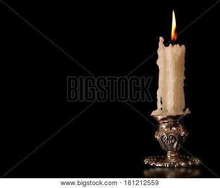 burning old candle vintage bronze candlestick. Isolated On Black Background.