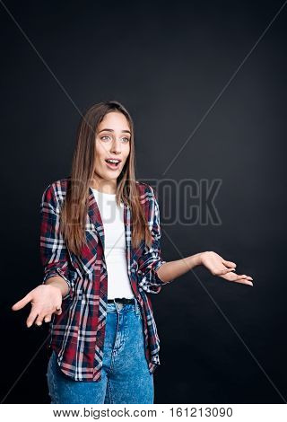 What a surprise.Pleasant surpriwed woman standing on black background and expressing wonder