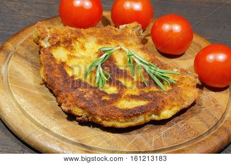 Cutlet with tomatoes garnished with rosemary on a plate