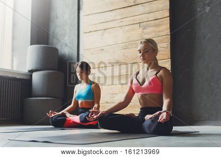Two young women in yoga class making exercises. Girls do meditation pose for relaxation. Healthy lifestyle in fitness club, backlight