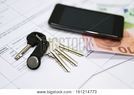House Keys On Documents With Mobile Phone