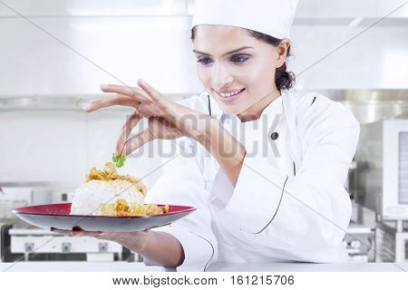 Portrait of an attractive Indian chef finishing dish while putting parsley leaf on food