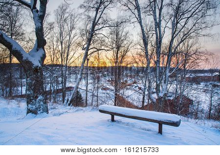 Winter sunset landscape with trees and wooden bench on the hill above city in Sweden, north scandinavian seasonal hipster background.