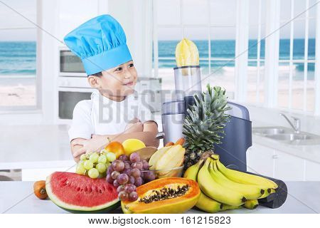 Photo of a little boy using a juicer machine to make fruits juice in the kitchen at home
