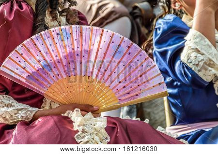 Cuidad Vieja, Guatemala - December 7 2016: Girl dressed in Spanish colonial dress holds fan on float in Virgin of the Immaculate Conception street parade