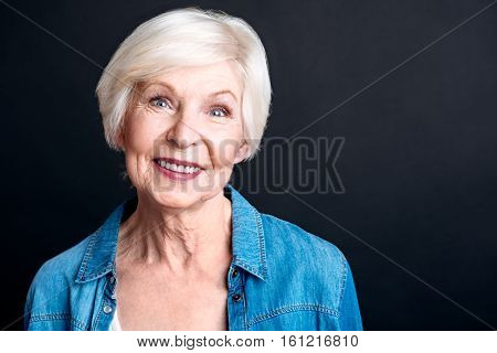 Happy retirement. Delighted aged pleasant woman smiling and lookign at you while expressing gladness