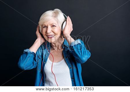 Dont stop the sound. Cheerful nice elderly woman smiling and listening to music while enjoying free time