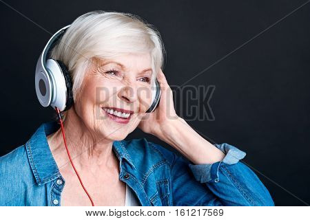 Feel younger. Cheerful delighted elderly woman wearing headphones and listening to music while standing on black background