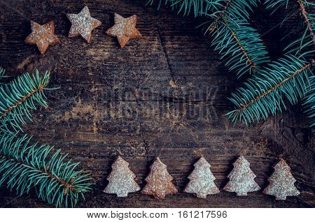 Christmas fir tree with gingerbread cookies on old wooden background with space for text. Merry Christmas and Happy New Year. Xmas concept. Top view. Copy space.