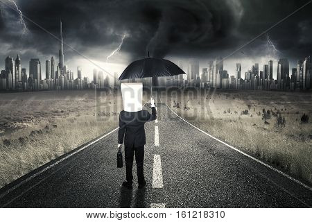 Male entrepreneur with cardboard head standing on the road while carrying umbrella and briefcase with thunderstorm in the sky